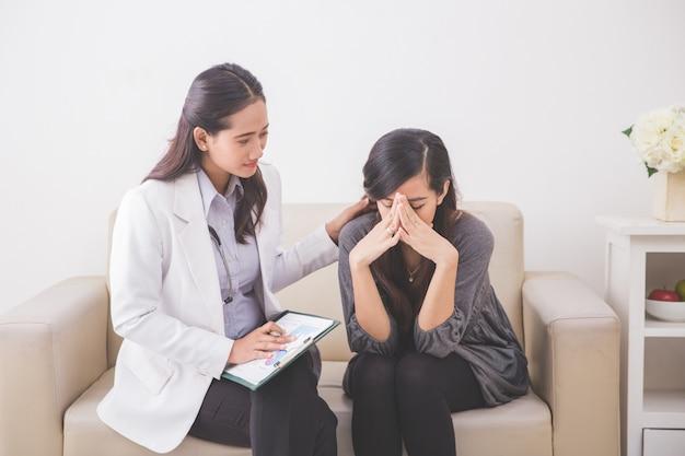 アジアの女性患者が女性医師と彼女の健康問題を相談しながら泣いています。