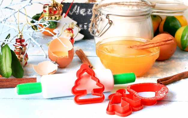 Новогоднее украшение инструментов для выпечки печенья образует скалку на светлом деревянном фоне селективного мягкого фокуса в деревенском стиле