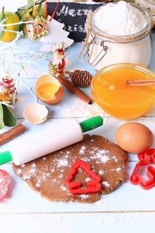 軽い木製の背景選択ソフトフォーカス素朴なスタイルにジンジャーブレッドクリスマスの自家製ケーキの生地を展開