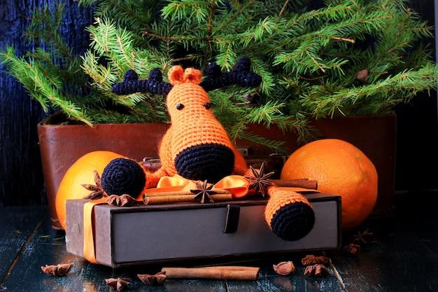 Новогодняя композиция олень в подарок под елку вручную вязаная игрушка корица, анис, мандарин, ель в винтажном стиле на старом деревянном фоне