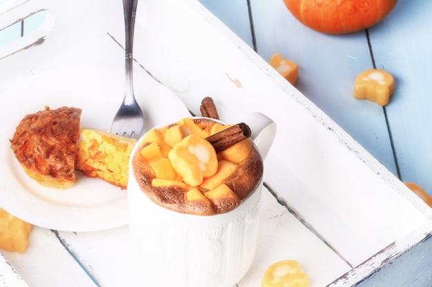 コーヒーとカボチャのマフィンの選択的なソフトフォーカス素朴なレトロなスタイルのトレイで朝食します。