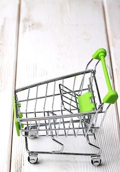 白い木製の背景の空っぽのショッピングカート