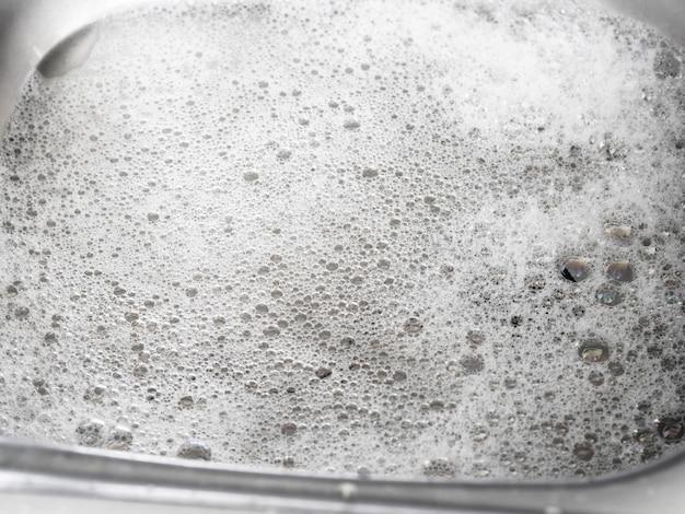 亜鉛の台所の流しで皿を洗った後の水と石鹸の泡