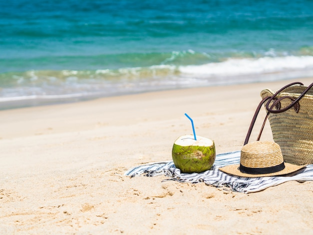 新鮮な若いココナッツを食べる準備ができて、青い海と砂浜のビーチでタオルの上に麦わら帽子と女性の麦わら帽子。熱帯の休暇旅行のコンセプトです。コピースペース
