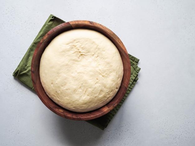 Пшеничная мука, дрожжевое тесто в деревянной миске