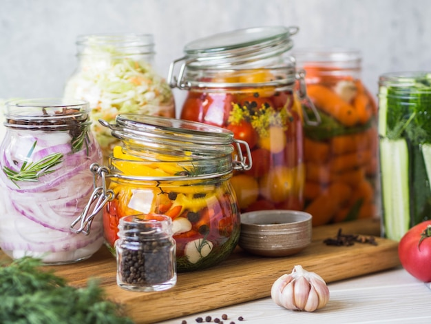 漬物の調理。長期保存のためにガラス瓶にさまざまな野菜を塩漬けします。ガラスの瓶に野菜を保存します。木の板に様々な発酵野菜