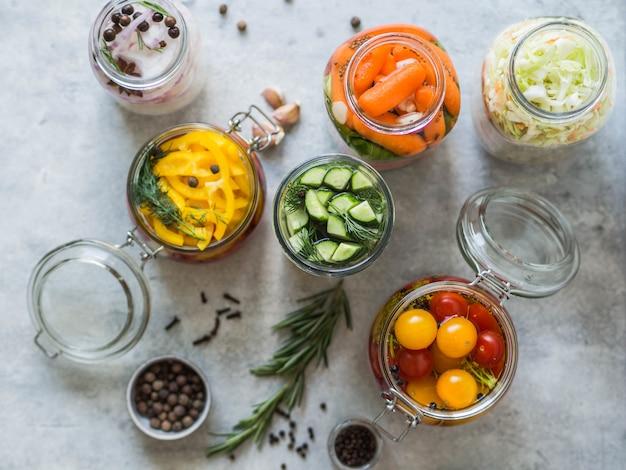 野菜の漬物。長期保存のためにガラス瓶にさまざまな野菜を塩漬けします。ガラスの瓶に野菜を保存します。さまざまなテーブルの上の緑の野菜を発酵させた。上面図。