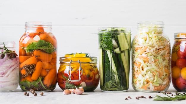 Маринованные овощи. соление различных овощей в стеклянных банках для длительного хранения. сохраняет овощи в стеклянных банках. разнообразие зеленые овощи на столе.