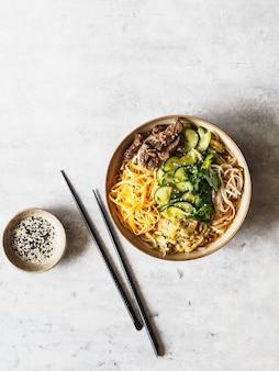 Холодный корейский суп кукси с овощами, яичницей, говядиной и лапшой в миске и палочками для еды. вид сверху
