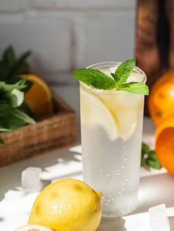 白いテーブルの上のガラスに氷と新鮮な夏の自家製柑橘類のレモネード。