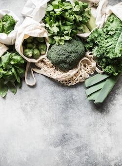 健康的なグリーンビーガンの食材。織物の袋に入ったさまざまなきれいな緑色野菜とハーブ