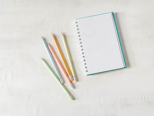 白紙のノートと色とりどりのグラファイト鉛筆
