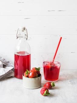 Клубничный напиток в стеклянной бутылке. прохладный ягодный компот в бутылке и стакан с соломой