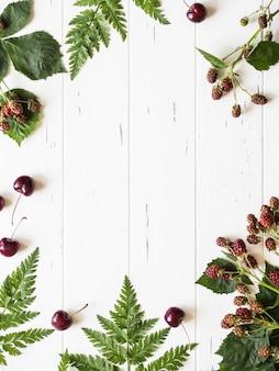 ブラックベリーの枝、シダ、素朴な白いウッドの背景に新鮮なチェリーの植物のフレーム構成。コピースペース