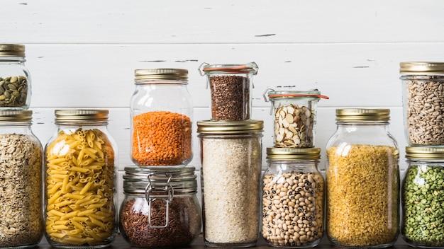 Различные крупы и семена в стеклянных банках на столе на кухне