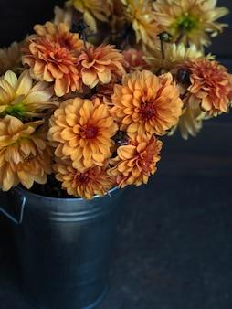 暗い背景に金属製のバケツで黄色とオレンジ色の庭のダリアの花