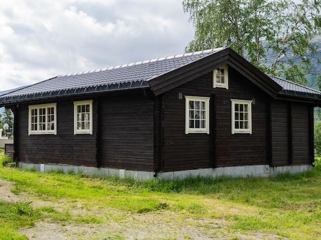 Традиционный коричневый деревянный скандинавский дом с белыми окнами в кемпинге на зеленой лужайке