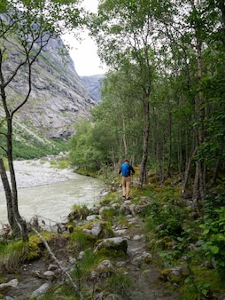 Неопределенный человек с туристическим снаряжением идет по камням в лесу в норвегии.