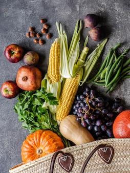 Плоские лежали сезонные овощи и фрукты на сером фоне