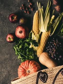 Соломенная сумка и свежие натуральные овощи и фрукты.