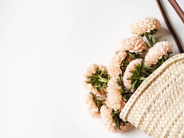 白い背景の枝編み細工品ストローバッグで季節の桃のアスターの秋の花束。上面図。コピースペース