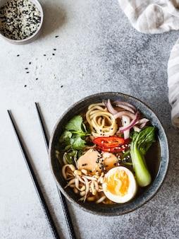 アジアのラーメン麺、鶏、朴菜キャベツ、灰色の背景に卵。