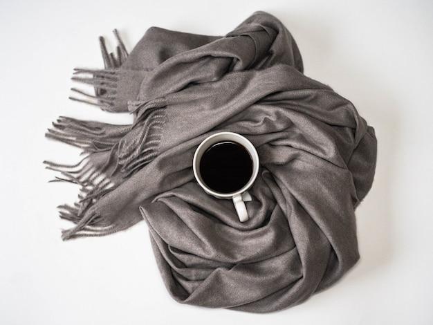 ブラックコーヒー入りの白いセラミックマグカップの周りの大きなダークグレーの暖かいスカーフ。寒い季節の暖かさと快適さ。ハグのコンセプト