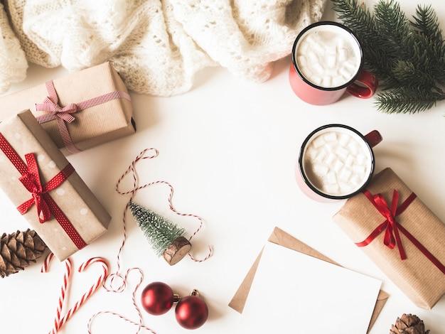 Две красные кружки с горячим напитком и зефиром, бумажная карточка для письма, конверт и рождественские украшения. квартира лежала для рождества или нового года. вид сверху. копировать пространство