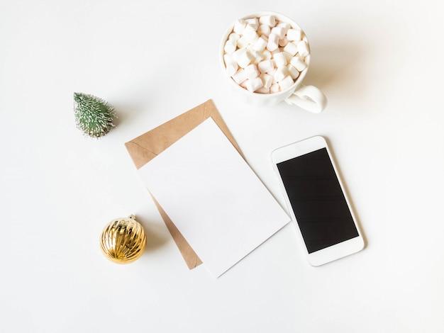 温かい飲み物とマシュマロ、手紙、封筒、白い電話、クリスマス装飾用の紙のカードと白いマグカップ