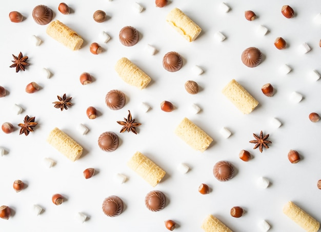 Сладкая праздничная композиция печенья с шоколадом, вафлями, зефиром и начинкой печенья на белом фоне. вид сверху