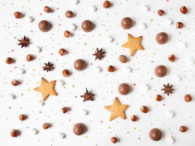 チョコレート、ナッツ、クッキー、スパイス、マシュマロ、ペストリー、白い背景の上にトッピングで甘いお菓子の組成。上面図