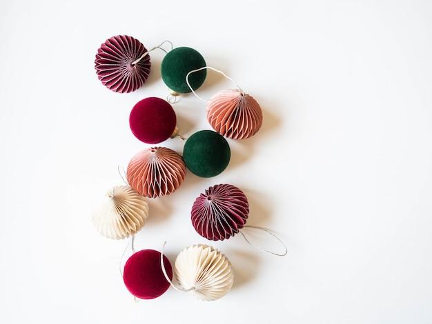 色とりどりの紙折り紙のクリスマスデコレーションと赤と緑のベルベットのクリスマスボール。コピースペース。上面図