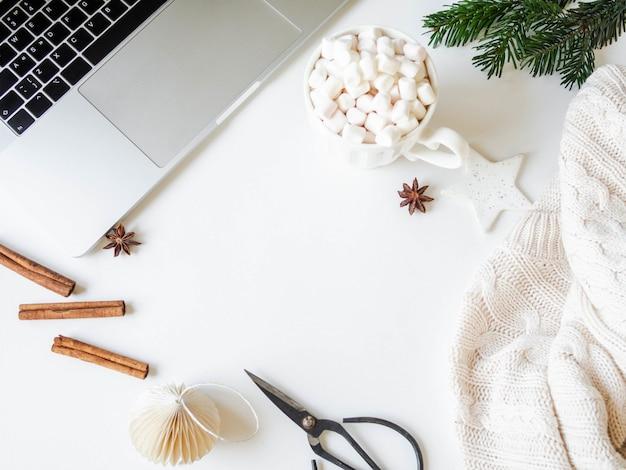 クリスマスデコレーション付きホームオフィスデスク、マシュマロ、ニットプルオーバー、スパイス入りの温かい飲み物とカップ。トップビュー、フラットレイアウト。