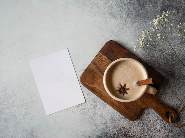 スパイス-アニススターとシナモンの棒と花と灰色の背景に白いカードとカプチーノコーヒーのカップ。