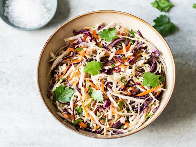 Красная капуста, морковь, салат из капусты салат из капусты в миску на сером фоне.