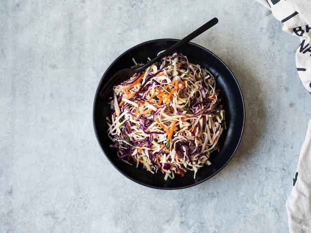 Красная капуста, морковь, салат из капусты салат из капусты на черной табличке на сером фоне. вид сверху
