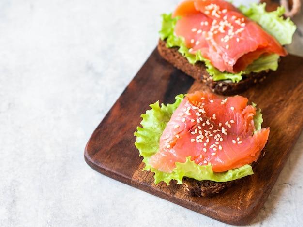Два тосты с кусочками лосося, кунжут и салат на деревянной доске на сером фоне.