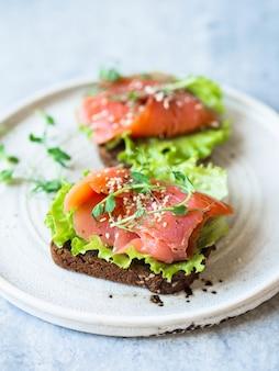 Два тосты с ломтиками лосося, кунжут, ростки гороха и салат на белой керамической пластине на сером фоне. копировать пространство