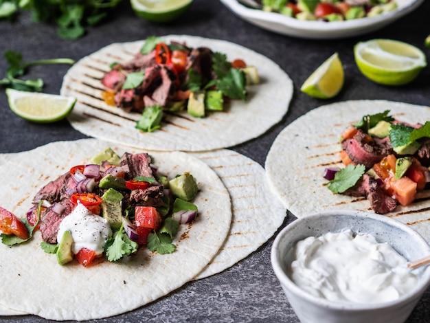 Тортилья с овощами и кусочками говяжьего стейка. авокадо, помидоры, красный лук, а также кинзу и сок лайма в лепешках. мексиканская еда.