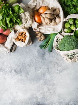 健康的な菜食主義の食材。編まれた袋の中の様々なきれいで健康的な野菜とハーブ。プラスチックなしの市場からの製品。ゼロ廃棄物コンセプトフラットレイアウト。コピースペース