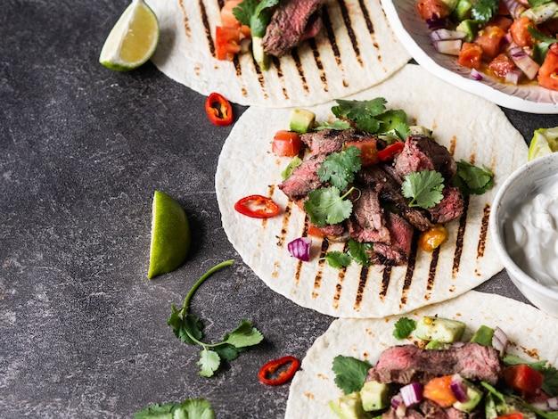 Тортилья с овощами и кусочками говяжьего стейка. авокадо, помидоры, красный лук, а также кинзу и сок лайма в лепешках. мексиканская еда. копировать пространство