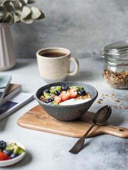 おいしい朝食-コーヒーとグラノーラ、ヨーグルトとベリー、テーブルの上のオープンマガジン。コピースペース。
