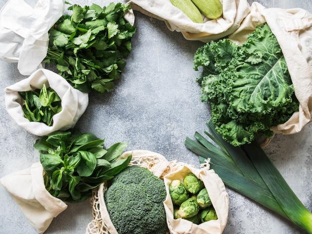 健康的なグリーンビーガンの食材。織物の袋に入ったさまざまなきれいな緑色の野菜やハーブ。プラスチックなしの市場からの製品。ゼロ廃棄物コンセプトフラットレイアウト。