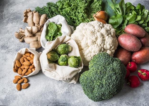 健康的な菜食主義の食材。様々なきれいな野菜や大理石の背景にハーブ。プラスチックなしの市場からの製品。フラットレイ