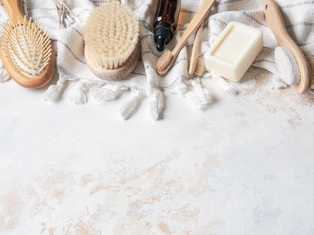 フラットには、さまざまなボディブラシ、白い綿のタオル、軽石、竹の歯ブラシ、アロマオイル、石鹸があります。廃棄物ゼロのコンセプト。環境に優しいバスセット。上面図
