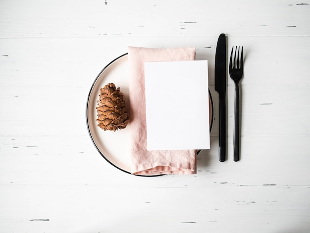 プレート、ピンクのナプキン、メニューカード、白い木製のテーブル上の機器とクリスマスの設定で素朴なテーブル。上面図。