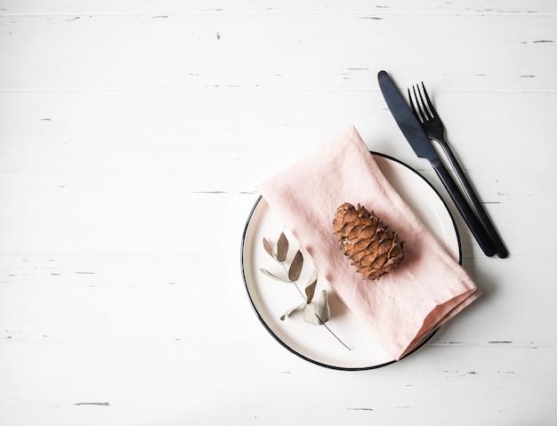 Деревенский сервировки с пластиной, розовые салфетки, конус, эвкалипт и приборы на белый деревянный стол. вид сверху.