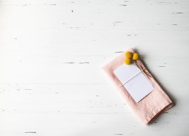 紙カード、ピンクのナプキン、白い木製テーブルの上の黄色い花を持つ素朴なロマンチックなテーブルセッティング。上面図。