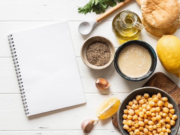 自家製の伝統的なフムスとレシピを書くための白いノートを調理するための食材のセット。コピースペース。