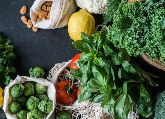 健康的な菜食主義の食材。様々なきれいな野菜、ハーブ、黒の背景上のナット。プラスチックなしの市場からの製品。平らに置きます。コピースペース